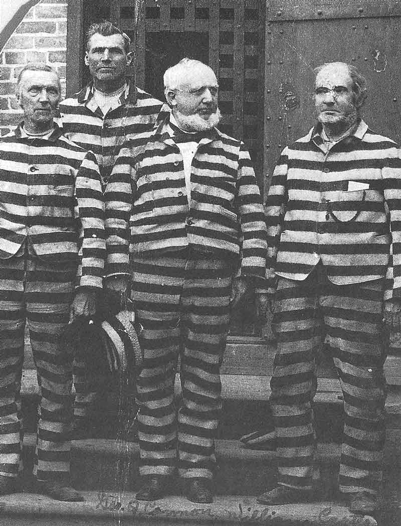 113. George Q. Cannon, center, first counselor in the First Presidency of the Mormon church, stands at the entrance to a prison cell block in this Savage photograph taken when the church leader was imprisoned in 1888 on federal charges of cohabitation.