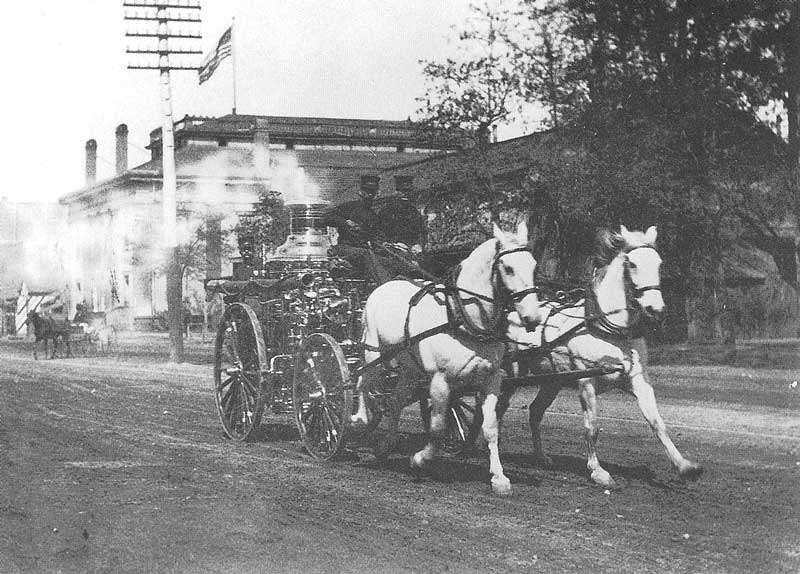 127. A horse-drawn fire engine races First South Street past the Salt Lake Theatre on its way to a fire.