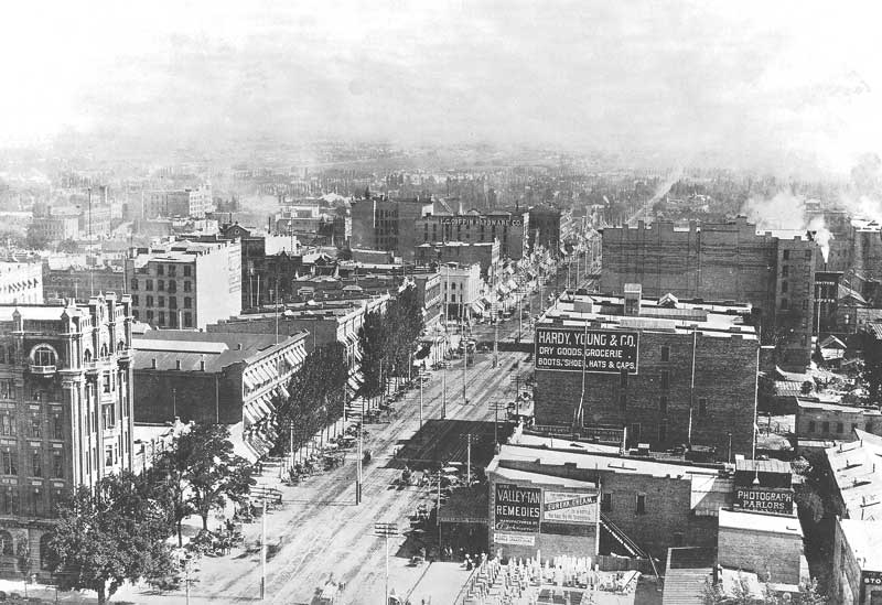 "[p.119] 129. From the top of the temple's center tower scaffolding, the photographer focused his camera on Main Street, looking south. In the lower right hand corner is Savage's gallery. Note the panes of the north light studio, just to the left of the ""Photograph Parlors"" sign."