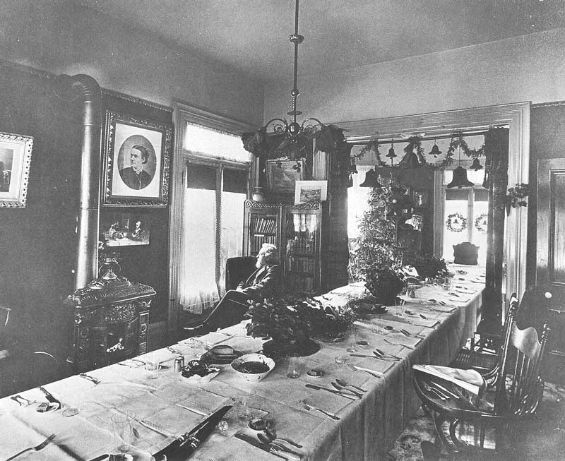 [p.123] 133. At Christmas time, C. R. Savage looks wistfully out the window of his homein a quiet moment at a family gathering. The table is set for a holiday family banquet.