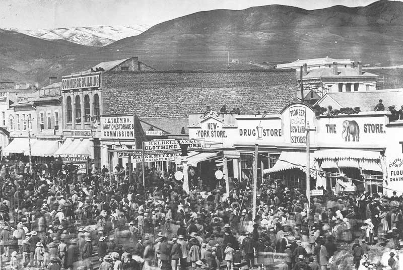 [p.133] 136. A crowd gathers on East Temple Street in 1868, about the time C. W. Carter opened his own photographic gallery. He captions this picture, &quot;A one-legged man walking a tightrope,&quot; hinting the crowd is awaiting a theatrical event.