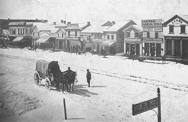 143. A covered wagon stops in the middle of a snow-covered East Temple Street in 1869. In the background are businesses located on the west side of the street.