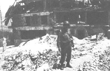 """""""Our outfit overran a Nazi concentration camp…. The Nazis had lined them up and shot them, and the bodies were still laying there."""" Freeman J. Byington in front of some bombed-out barracks that had housed German SS troops, describing the scene he photographed in the next picture."""