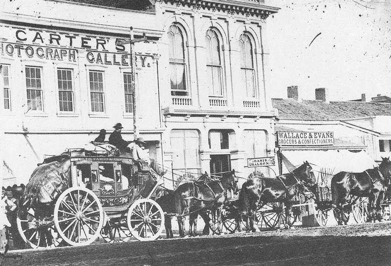 "159. A photograph of a stagecoach in front of Carter's 1868 gallery shows a canvas banner over ""Sutterley Brothers Photograph Gallery."" Carter took over their facilities when J. K. Sutterley left the city that year."