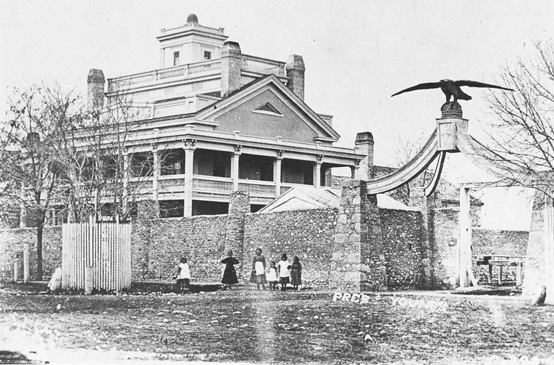[p.160] 172. An early view of the Beehive House, residence of Brigham Young, was probably taken around 1868, after the wall and Eagle Gate entrance were installed.