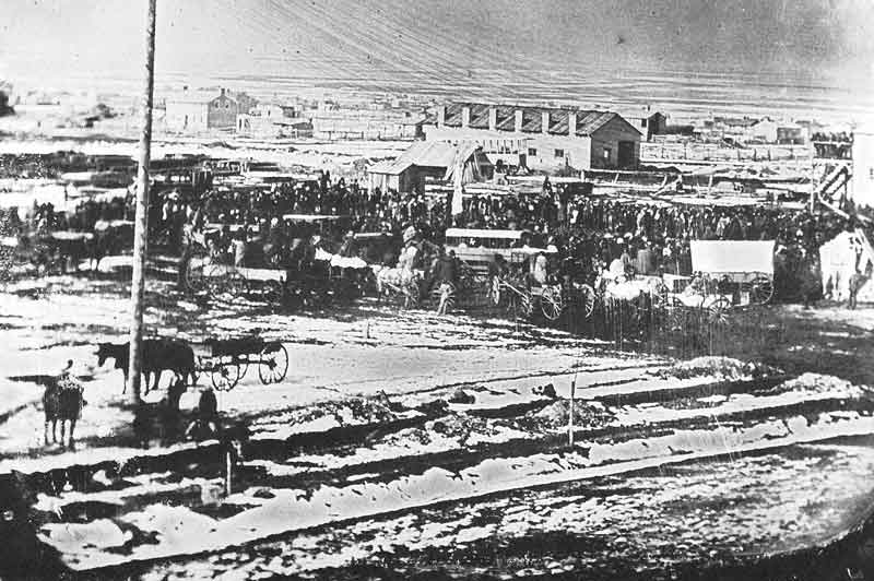 19. A crowd gathers on the Temple Block to break ground for the Salt Lake Temple on 14 February 1853. This photograph, reproduced from the original daguerreotype, was taken by Marsena Cannon, the first known photographer in Utah. He was stationed with his camera atop a building across the street.