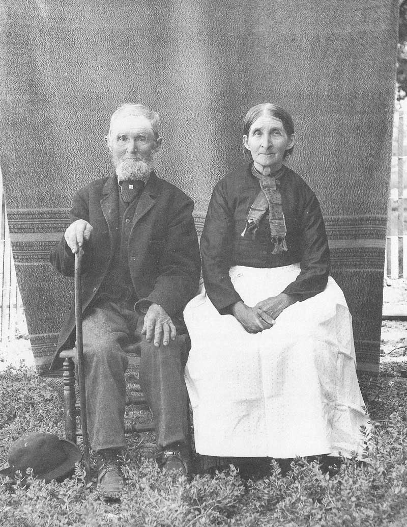 [p.184] 192. An unidentified couple in a small central Utah town pose in front of an old blanket draped over a clotheline in their yard.