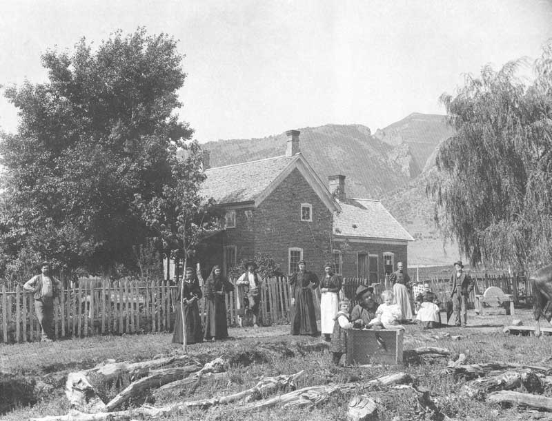 [p.191] 198. The Draper family in front of their home in Freedom, Sanpete County, about 1890. In the foreground they display a pet magpie in a cage. Anderson was skilled at arranging people naturally in front of their homes.