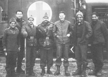 """""""I remember the uncertainty of the natives. They had little paper flags and they weren't quite sure… whether to put out a flag for North Korea or South Korea, for the United States, for the United Nations, or …for China:"""" David R. Lyon (fifth from left) with a medical team from India."""