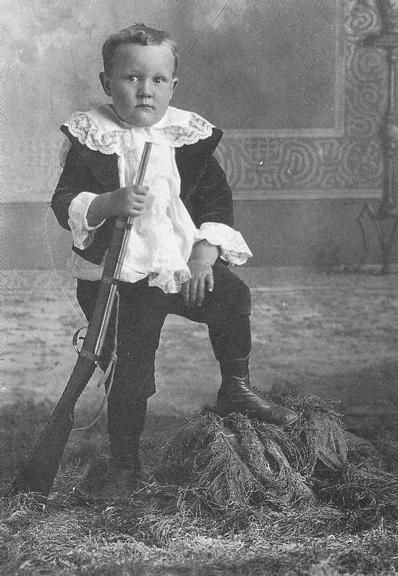 200. The son of Mrs. Julia Biddle of Emery is holding a rifle.