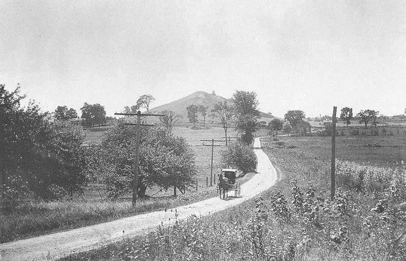 228. A buggy rolls down a winding road at the base of Hill Cumorah in 1907. The hill is sacred to Mormons because that is where Joseph Smith is said to have unearthed the plates from which the Book of Mormon was translated.