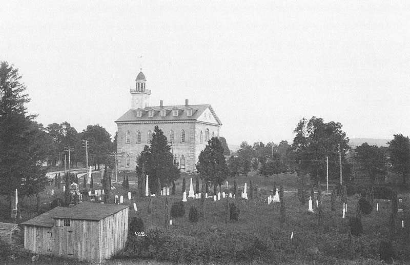 230. On 7 August 1907, Anderson photographed the Mormon temple in Kirtland, Ohio, from the cupola of a nearby barn, looking across the cemetery and showing the northwest front of the temple.