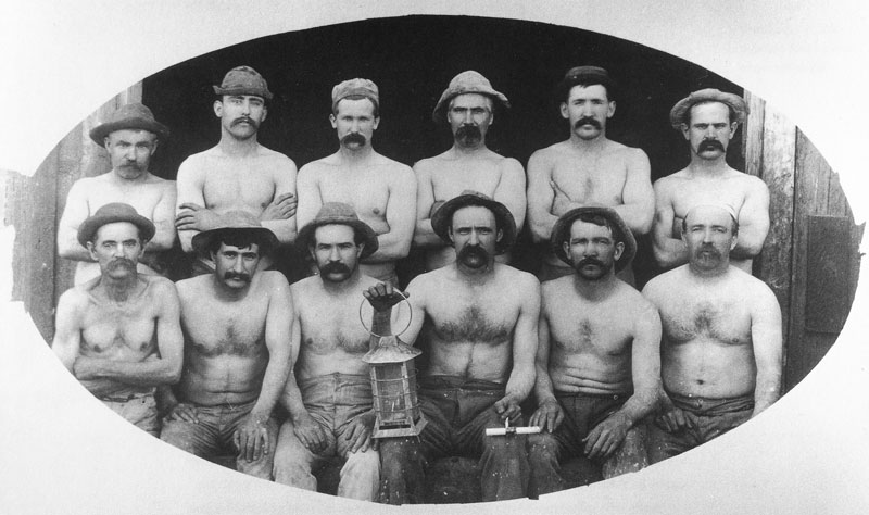[p.251] 261. Stripped to the waist, Cornish miners shortly before they descend into one of the Comstock Lode mines in Virginia City. Crockwell used this picture in both his Virginia City and Park City souvenir booklets.