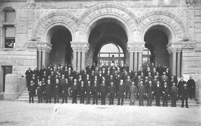 [p.276] 282. Members of the Utah Constitutional Convention on the steps of the Unihalle (Salt Lake City-County Building) in 1894. John Henry Smith, the white-haired, bearded man (standing center), chaired the convention. Photographer Charles William Symon, the only man in the picture wearing a hat, three rows behind Smith, and a little to the right, also served on the convention, which drafted Utah's constitution.