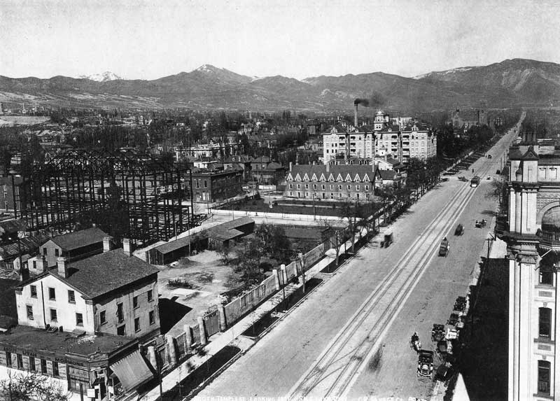 [p.310] 312. With the superstructure of the Deseret Gymnasium in the background, Johnson's photo store and gallery on the corner (lower left) was beginning to look rundown in 1910 when the LDS church asked Johnson to vacate the building to make way for the new Hotel Utah.