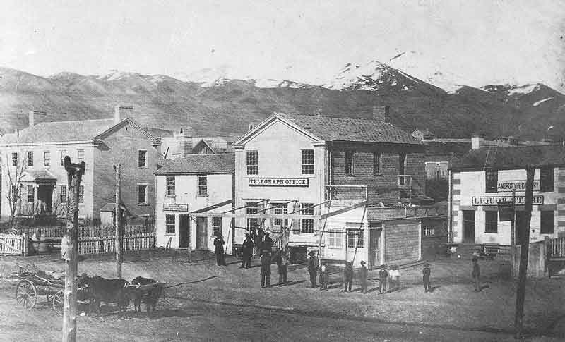 52. Snow-covered peaks of the Wasatch Mountains serve as a backdrop for this view of East Temple Street after 1861. The telegraph office was located on the east side of the street, between South Temple and First South. This Marsena Cannon view was in the 1879 Barfoot photographic exhibit.