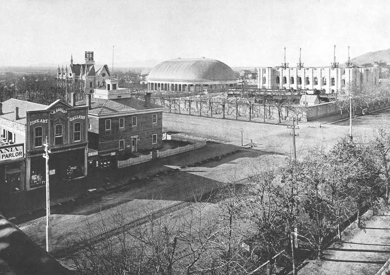 "[p.96] 107. Savage's ""Fine Art Gallery,"" left, is one of the principal downtown businesses about 1880. In the background the Assembly Hall, which replaced the Old Tabernacle, is still under construction. It was dedicated in 1882."